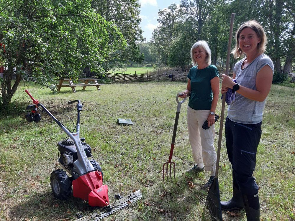 Foto på två medlemmar i Stranda naturskyddsförening som just har slagit gräset på Guttorp.